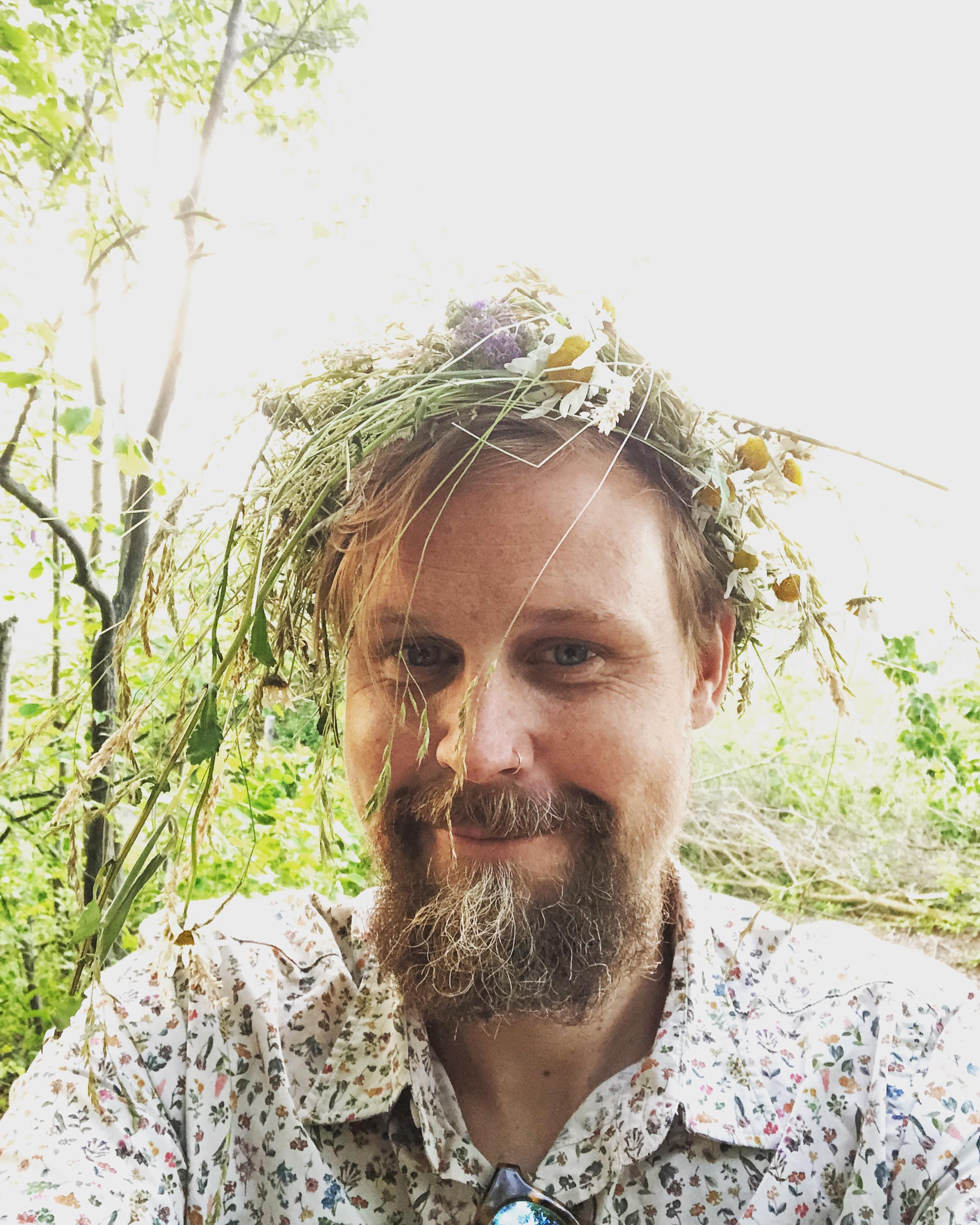 Michael wearing a flower crown at a Swedish folk music midsummer celebration